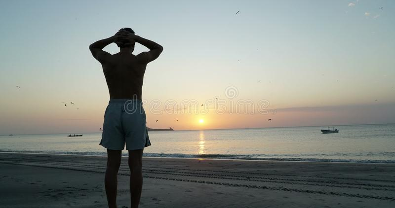 El hombre en la playa tropical que mira puesta del sol, medita se relaja, terapia psicológica, reflexión imagen de archivo libre de regalías