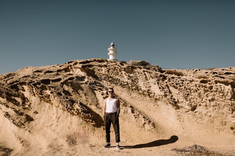 El hombre en la playa Un hombre cerca de los acantilados arenosos El hombre en el fondo del faro Faro foto de archivo libre de regalías