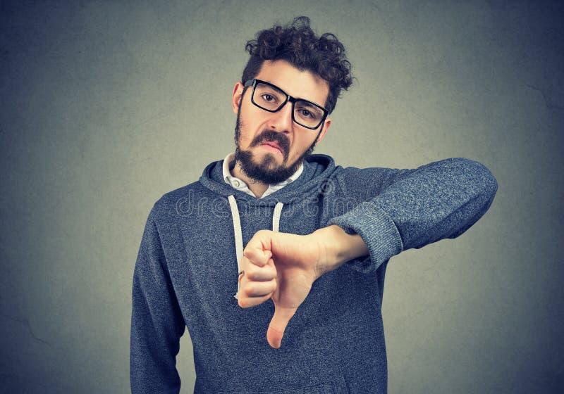 El hombre en las lentes que muestran la aversión con el pulgar abajo gesticula imagenes de archivo
