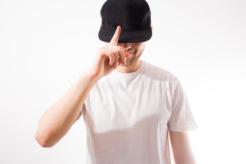 El hombre, en el negro en blanco, gorra de béisbol, snapback en un fondo blanco, mofa para arriba, espacio libre, presentación de foto de archivo