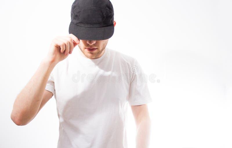 El hombre, en el negro en blanco, gorra de béisbol, snapback en un fondo blanco, mofa para arriba, espacio libre, presentación de imagen de archivo