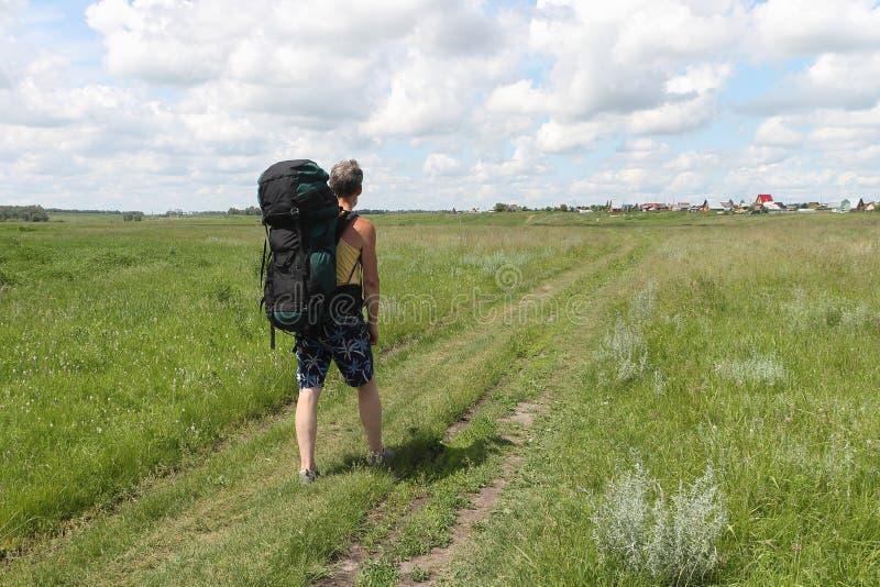 El hombre en pantalones cortos con una mochila que va en el camino rural foto de archivo libre de regalías