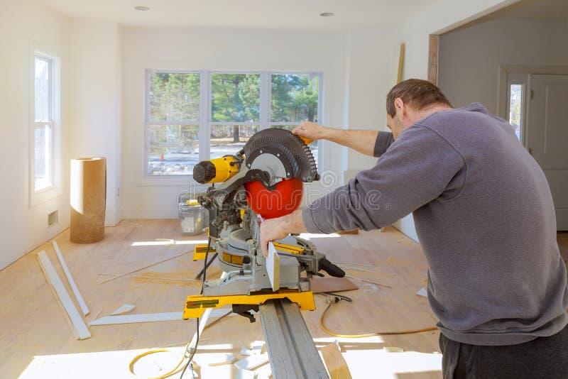 El hombre en sierras del constructor del carpintero de la profesión con una circular vio un moldeado bajo del ajuste de madera foto de archivo