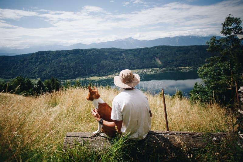 El hombre en sombrero se sienta con el perrito del perro del mejor amigo en la parte superior foto de archivo