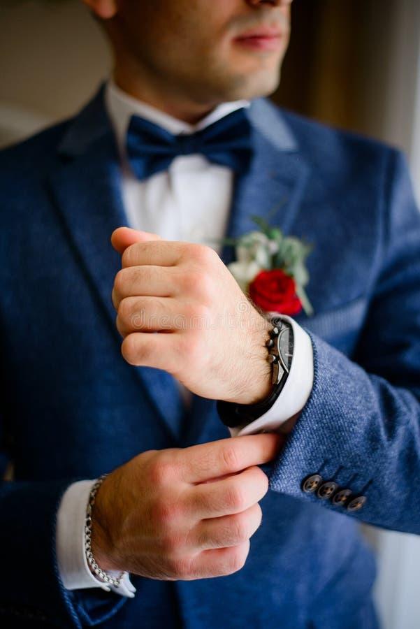 El hombre en traje azul ajusta la manga blanca sobre el reloj fotografía de archivo libre de regalías