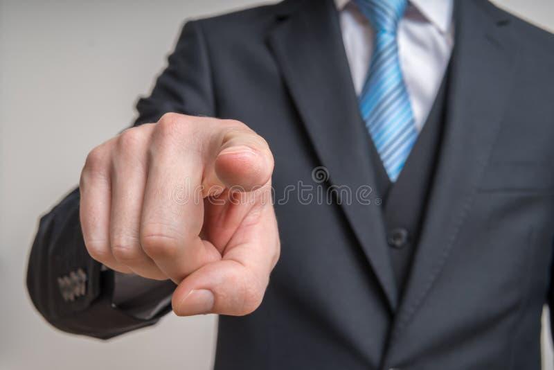 El hombre en traje está mirando la cámara y está señalando hacia usted imagen de archivo libre de regalías