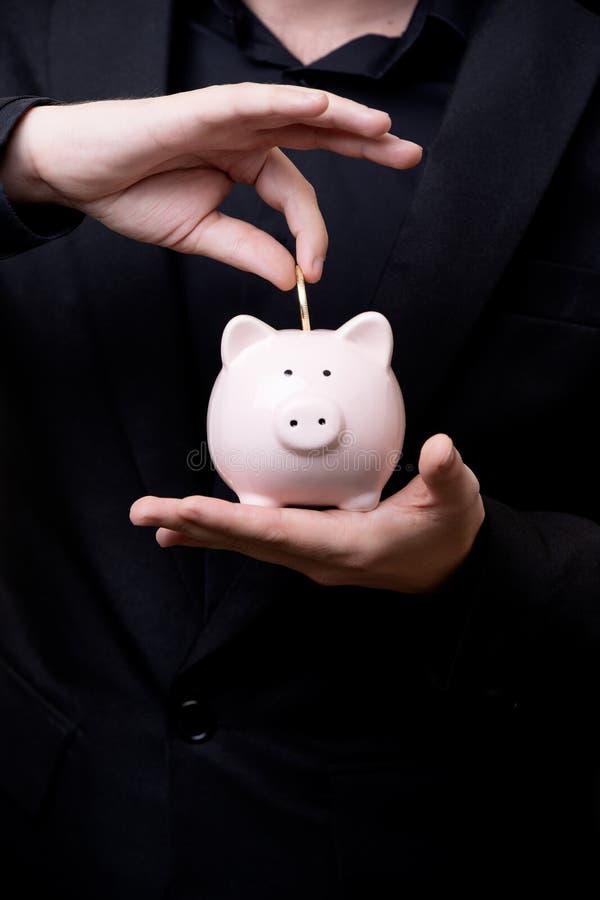 El hombre en traje negro pone la moneda en la hucha fotografía de archivo libre de regalías