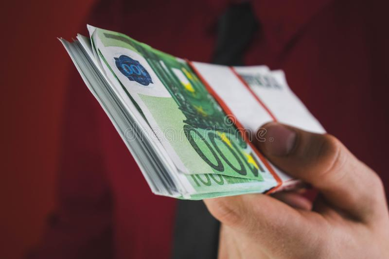 el hombre en traje rojo lleva a cabo hacia fuera un taco del dinero en su mano en fondo rojo imagenes de archivo