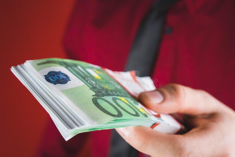 el hombre en traje rojo lleva a cabo hacia fuera un taco del dinero en su mano en fondo rojo imágenes de archivo libres de regalías