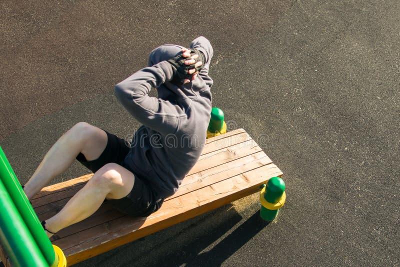El hombre, en un banco inclinado, realiza los ejercicios, torciendo en una prensa, al aire libre, la visión superior fotos de archivo