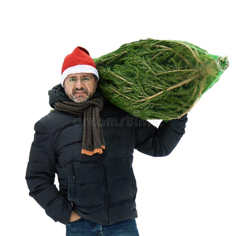 El hombre en un sombrero rojo de Papá Noel lleva un árbol de navidad lleno en una rejilla aislado en blanco foto de archivo libre de regalías
