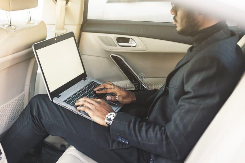 El hombre en un traje de negocios escribe en el ordenador portátil en el salón de un coche costoso con el interior de cuero fotos de archivo