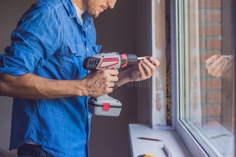 El hombre en una camisa azul hace la instalación de la ventana imágenes de archivo libres de regalías