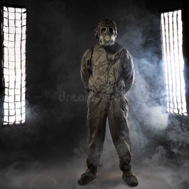 El hombre en una careta antigás en humo foto de archivo libre de regalías