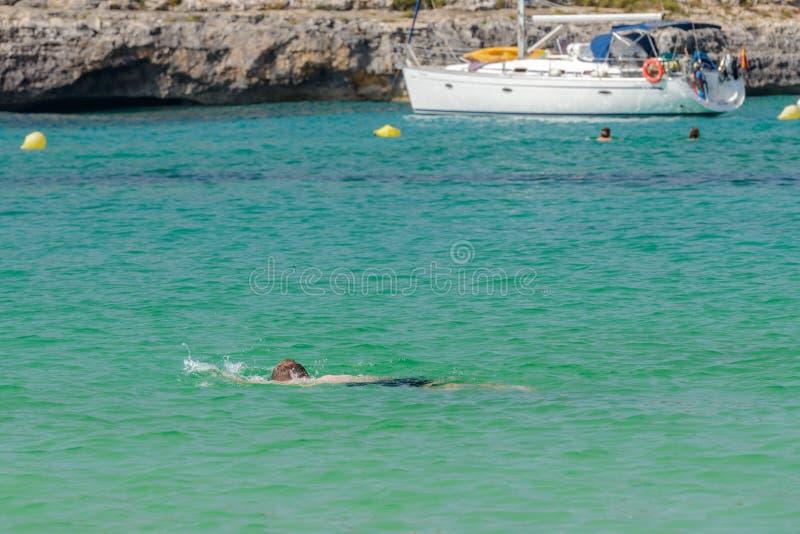 El hombre en una máscara del equipo de submarinismo nada en agua de mar azul fotos de archivo