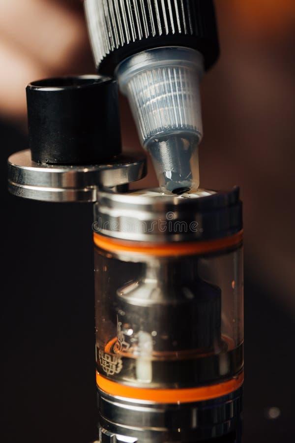 El hombre en una tienda del vape está llenando un líquido especial en e-cigarrillo fotografía de archivo libre de regalías