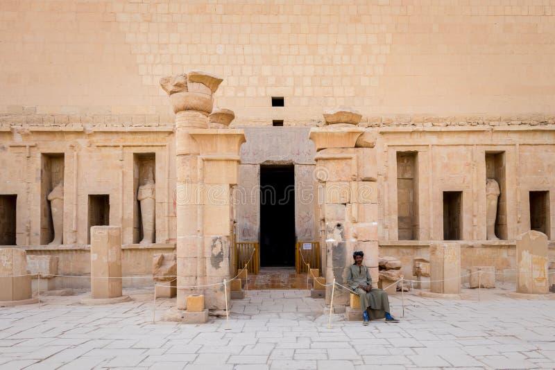 El hombre en vestido egipcio tradicional se sienta en la entrada al templo de Hatshepsut fotos de archivo