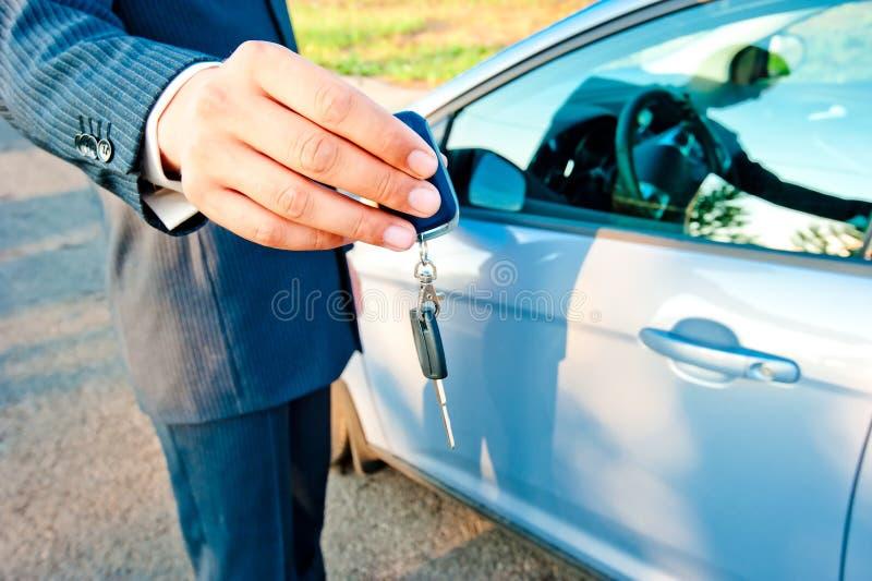 el Hombre-encargado transmite la llave al nuevo comprador del coche fotografía de archivo libre de regalías