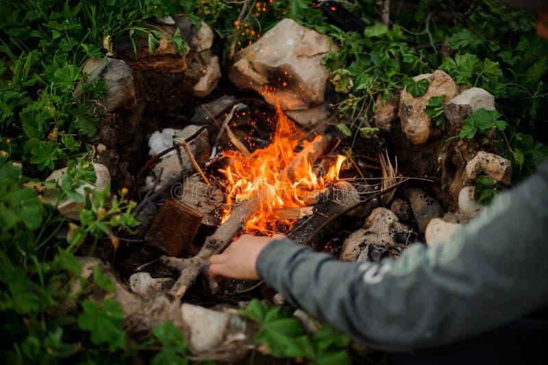 El hombre enciende el fuego en un campo turístico foto de archivo libre de regalías