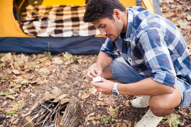 El hombre enciende la hoguera en el bosque foto de archivo libre de regalías