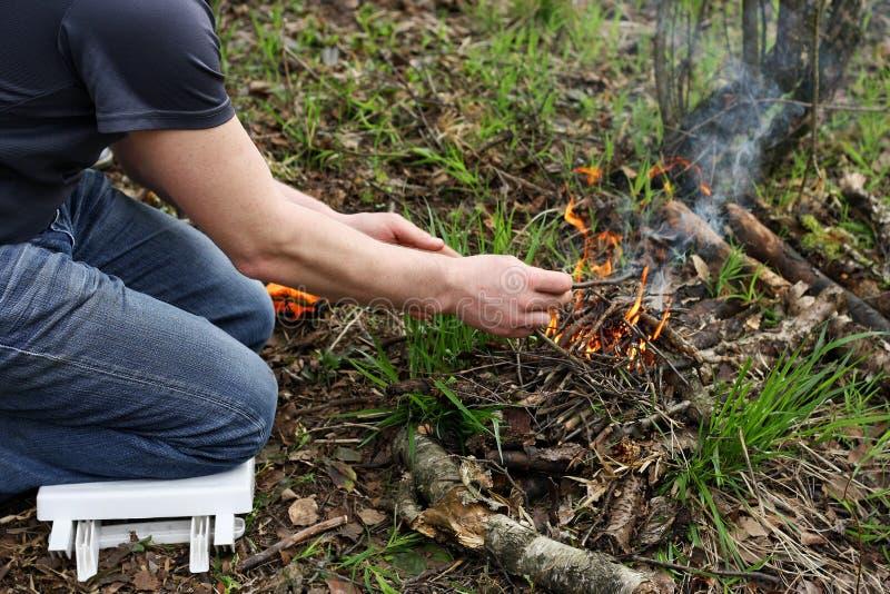 El hombre enciende un fuego en el bosque fotos de archivo