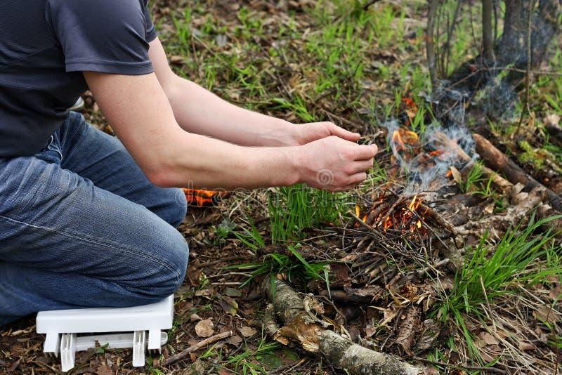 El hombre enciende un fuego en el bosque imagen de archivo libre de regalías