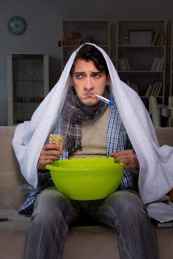 El hombre enfermo que hace la inhalación en la noche en hogar foto de archivo