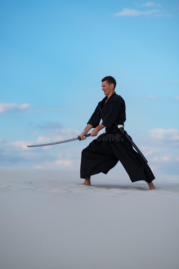 El hombre enfocado está entrenando a artes marciales en desierto imagen de archivo