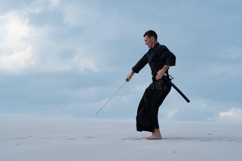 El hombre enfocado está practicando artes marciales en el desierto fotos de archivo libres de regalías