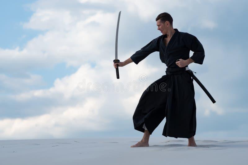 El hombre enfocado está practicando artes marciales japoneses imágenes de archivo libres de regalías