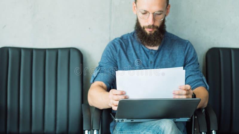 El hombre enfocado leyó la información de los documentos de negocio fotos de archivo