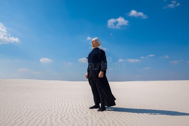 El hombre enfocado que se coloca en el desierto y medita imagen de archivo
