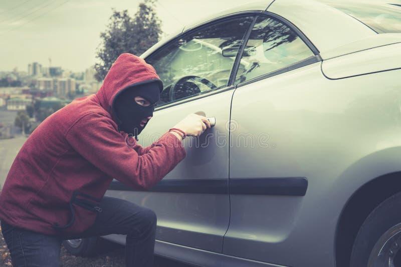 El hombre enmascarado en ropa de sport escoge furtivamente la cerradura del coche en un fondo de la ciudad Del ladrón picklocks m imágenes de archivo libres de regalías
