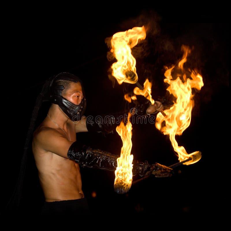 El hombre enmascarado hace girar el fuego en el festival que hace juegos malabares de Goa imagen de archivo