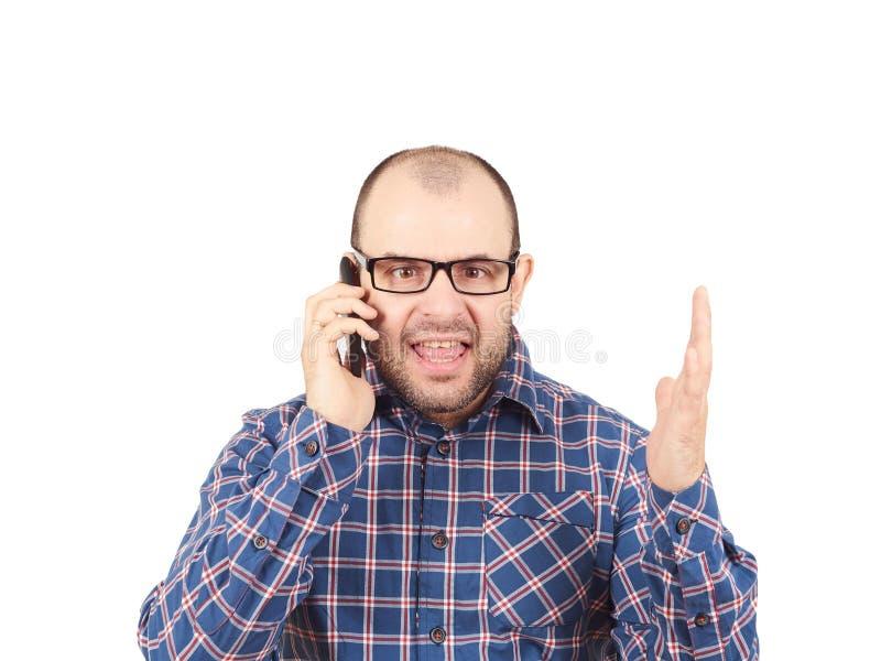 El hombre enojado en vidrios grita en el teléfono imágenes de archivo libres de regalías