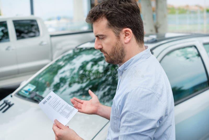 El hombre enojado encuentra que expiró la multa de aparcamiento después del límite de tiempo que parqueaba fotos de archivo