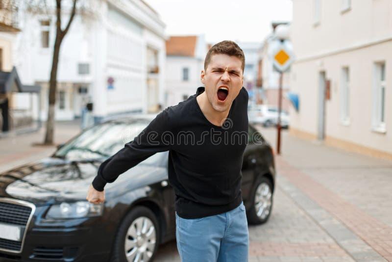 El hombre enojado grita cerca de un coche en la ciudad imagen de archivo