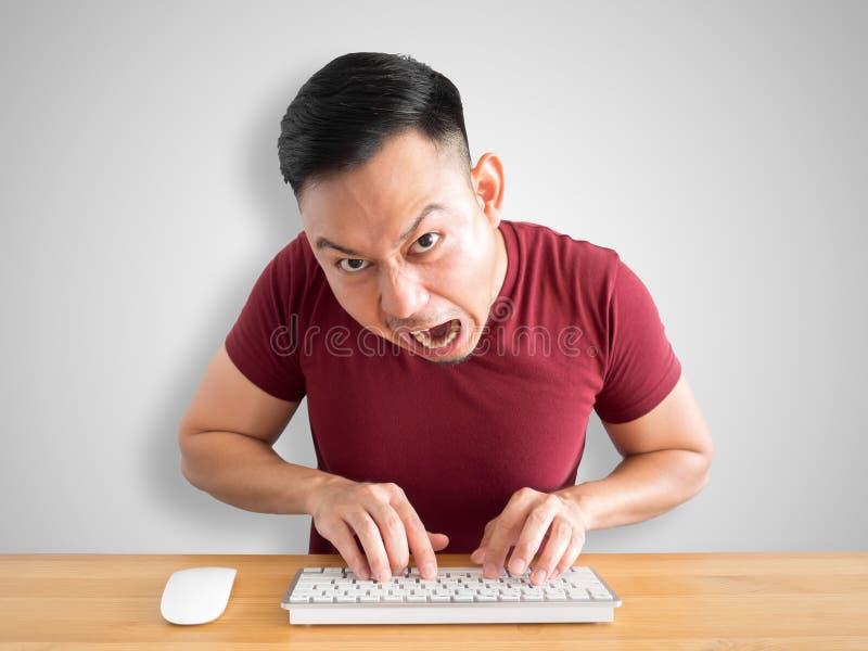 El hombre enojado y furioso trabaja con el ordenador imagenes de archivo