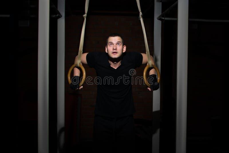 El hombre entrena en el gimnasio en los anillos para la gimnasia imagen de archivo