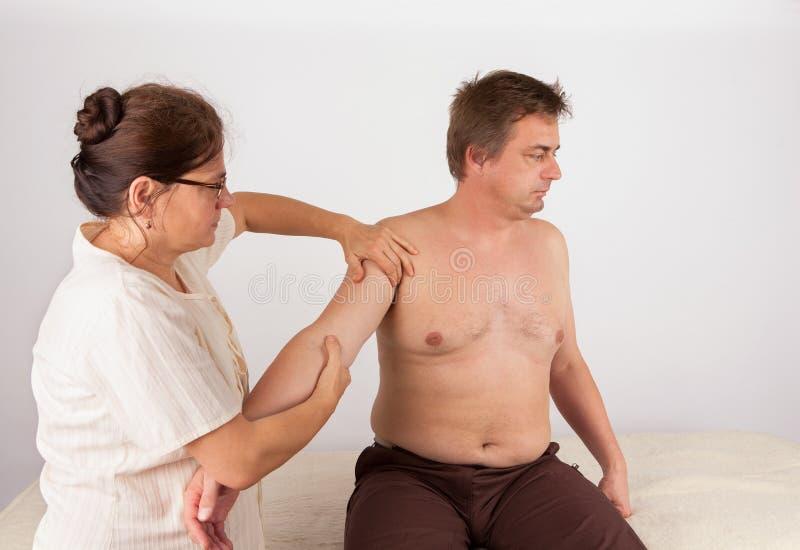 El hombre envejecido centro recibe bowen el tratamiento del masaje para su brazo imagen de archivo