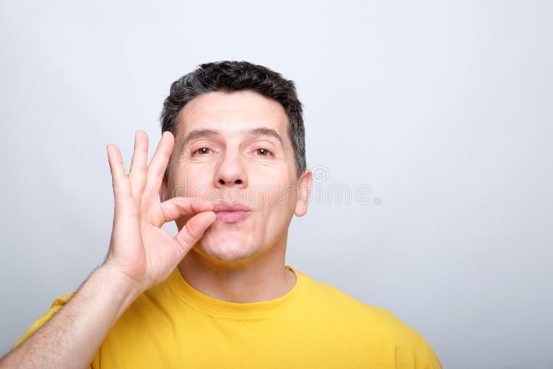 El hombre envejecido medio blanco se besa los fingeres como muestra de delicioso imagen de archivo libre de regalías