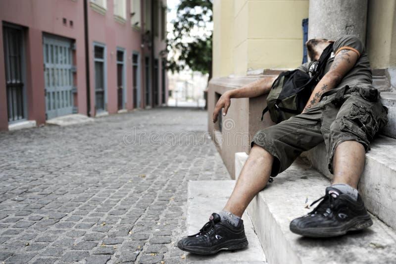 El hombre enviciado a las drogas miente en un doorste fotografía de archivo libre de regalías