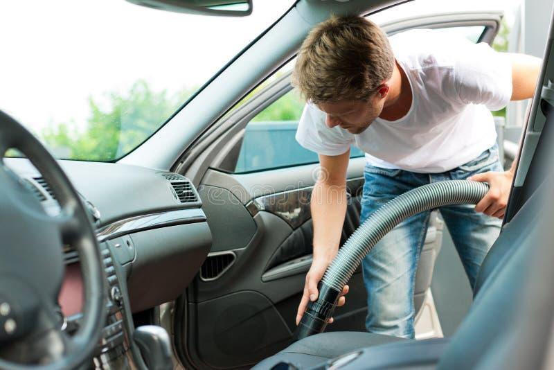 El hombre es hoovering o de limpieza del coche foto de archivo