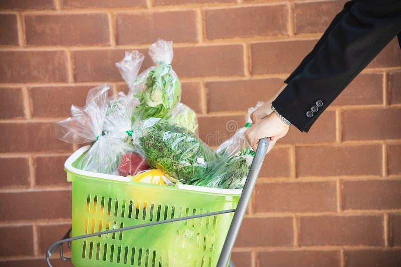 El hombre es verduras frescas que hacen compras en tienda del supermercado imagenes de archivo