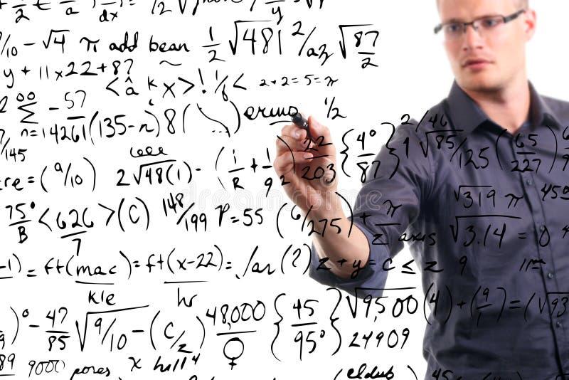 El hombre escribe ecuaciones matemáticas en whiteboard imágenes de archivo libres de regalías