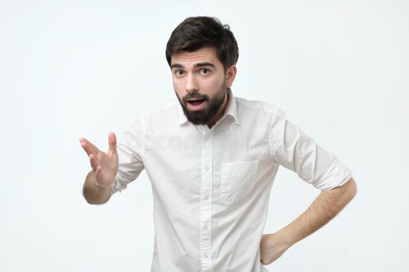 El hombre español joven con la barba negra está gesticulando activamente fotos de archivo libres de regalías