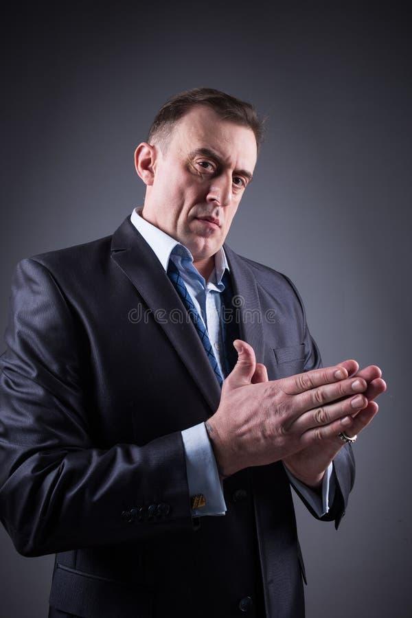 El hombre espantoso frota sus manos fotos de archivo