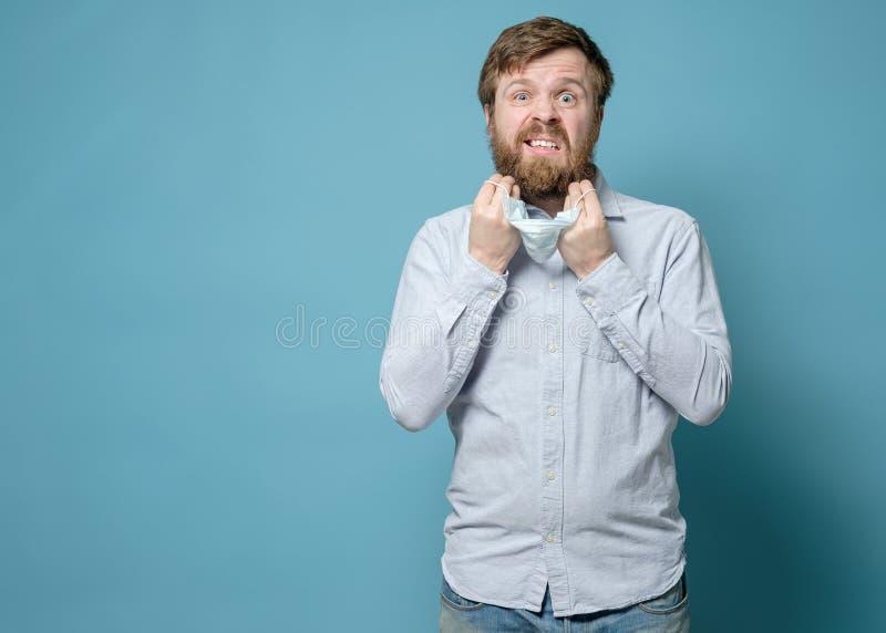 El hombre está alarmado de que la máscara médica no encaje en la cara por la barba Copiar espacio Concepto de seguridad durante l foto de archivo