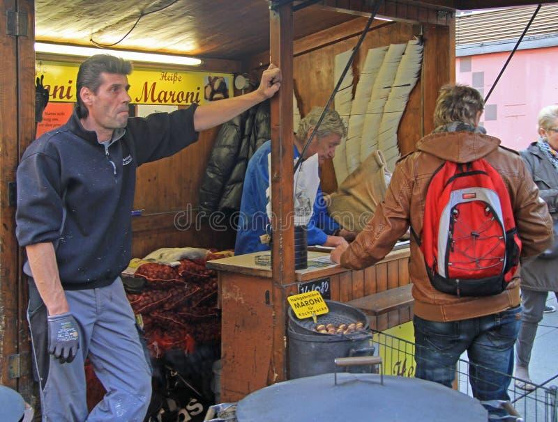 El hombre está comprando la castaña frita en Graz, Austria imagen de archivo libre de regalías