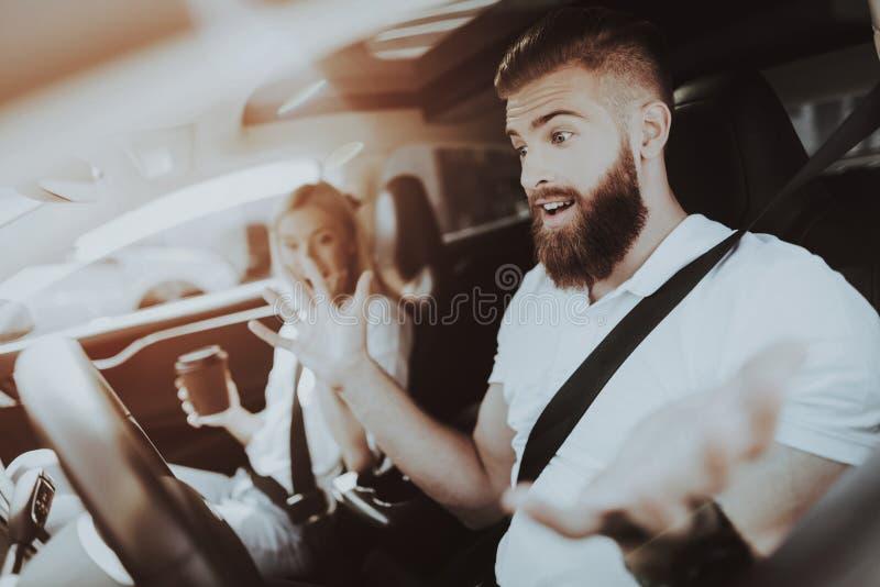 El hombre está conduciendo un coche de Tesla Muchacha en Front Seat foto de archivo libre de regalías